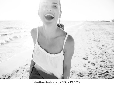 wonderfully cheerful mood. Portrait of smiling young woman in dress on the beach in the evening having fun time