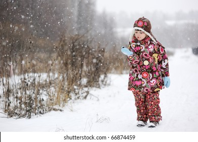 Wondering Small girl in colorful snowsiut catches snowflakes in strong snow fall