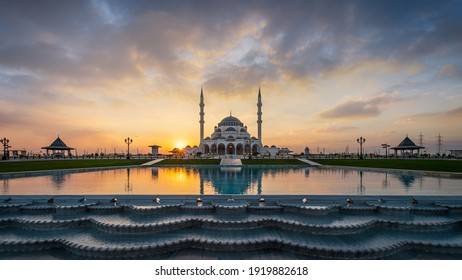 The wondrous Sharjah Mosque reflected in the pool waters on background of the cloudy sunset sky
