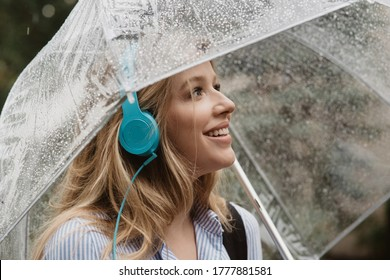 Wondrous young woman listening to music in headphones with rainy weather under an umbrella