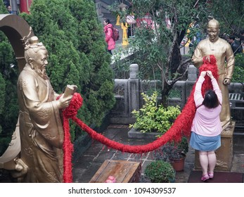 Wong Tai Sin,Hong Kong-January 6 2018: A woman ties a knot of red rope at Yue Lao , the famous Chinese holy god golden statue, which is well known for love and marriage prayers answered.