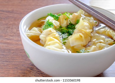 wonton and dumpling in clear soup on table