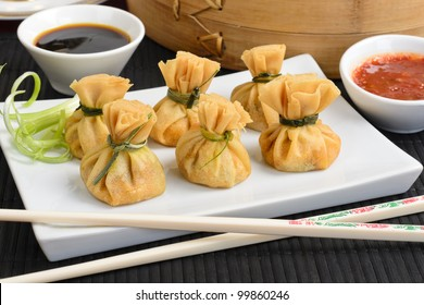 Wonton - Oriental deep fried wontons filled with prawn and spring onion, served with dumpling and chili sauces.