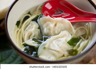 Wonton soup with egg noodles in a bowl, close-up, selective focus