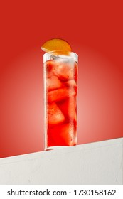 Woo Woo cocktail in a highball glass on a simple red background