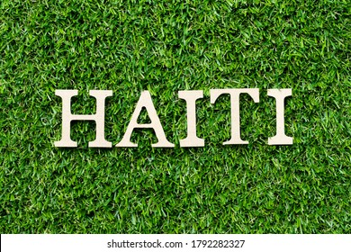 Wood alphabet letter in word Haiti on green grass background