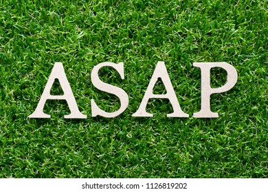Wood alphabet in word ASAP (Abbreviation of as soon as possible) on artificial green grass background