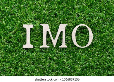 Wood alphabet in word IMO (abbreviation of in my opinion) on artificial green grass background