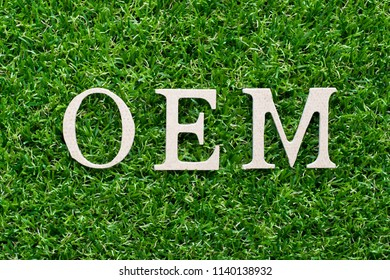 Wood alphabet in word OEM (Abbbreviation of Original Equipment Manufacturer)on artificial green grass background