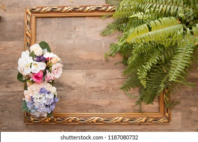 Wood background in a frame with palm leaves and flowers