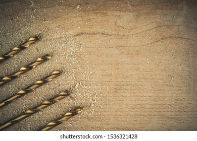 Wood background with golden drill bits on the left side. Copy space on the right side.