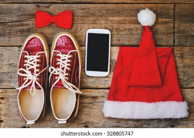 wood background with phone sneakers red hood and a bow. toning. selective focus