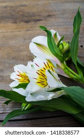 Wood background with white lilies bouquet
