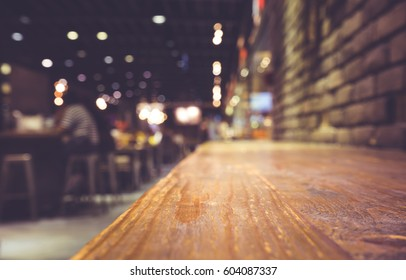 Wood bar (table) on cafe in dark night with people and light background/selective focus. For montage product display
