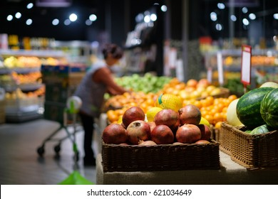 Wood baskets with pomegranate, watermelon and oranges in modern supermarket