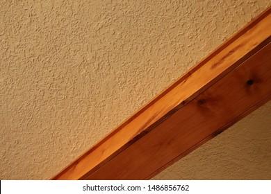 Wood beam against cream ceiling