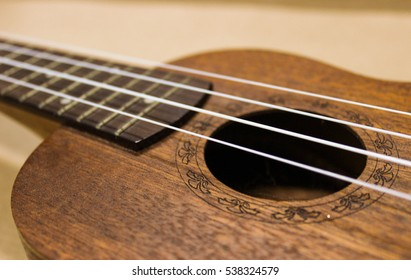 Wood beautiful Ukulele. Four strings guitar. Hawaii guitar. Beginner musician. Ukulele closeup.
