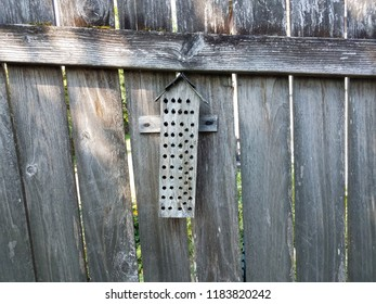 wood bee house with holes on wooden fence