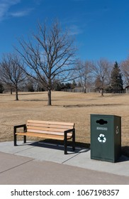 Wood bench next to green recyle bin with tree in background on a blue sky day at local park in Colorado.