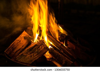 Wood billets burning with orange hot fire flames in night outdoor