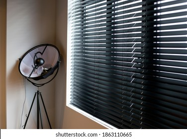 Wood blinds Coulisse black color closeup on the window in the interior. Wooden slats 50mm wide, black tapes. Venetian blinds closed in the room. There is a floor lamp near the window.
