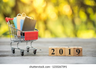 Wood block 2019, shopping cart, and shopping bags using as background. Black Friday, boxing day, mid year sales,and year end sales.