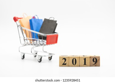 Wood block 2019, shopping cart, and shopping bags isolated on white background using as background. Black Friday, boxing day, mid year sales,and year end sales.