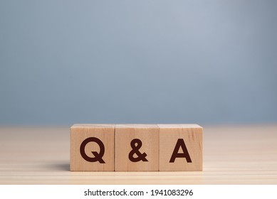 wood block cube with alphabet Q and A on wooden table,Questions and answers concept.