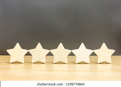 Wood block five star shape on wooden table gray background. 5 stars. Concept excellent rated services.