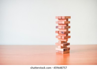Wood block Stack tower game for children playing on wooden table with copyspace
