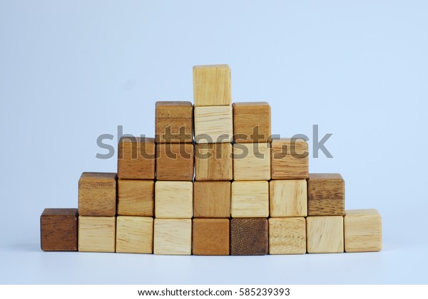 Wood block step stair of pyramid on gray background. Business concept for growth success process. Selective focus on the top step, copy space for your text or design.