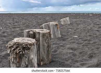 Wood blocks on black sand beach, Reunion Island, France
