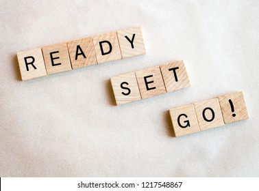 Wood blocks spell Ready Set Go! on a white background. Education and business concepts