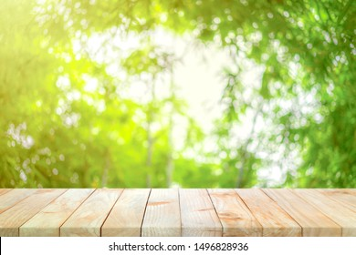 Wood board on the bamboo garden defocus blur background in the noon with orange - yellow sunlight from corner of image. This background can be used for packaging shot or natural product launch.