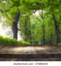 wood board table in front of spring park alley trees background. Ready for product display montages