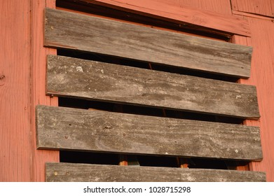 wood boards covering window red barn