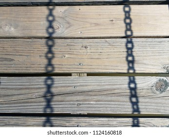 wood boards with shadows of metal chains