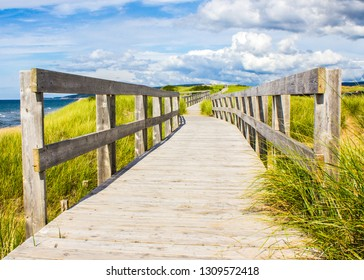 Wood boardwalk at Inverness Beach on Cape Breton Island, Nova Scotia on summer day.