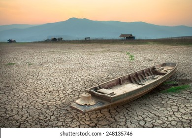 The wood boat on cracked earth, metaphoric for climate change and global warming.