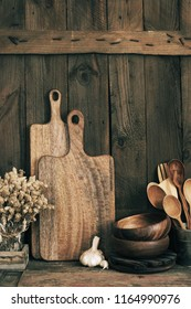 Wood bowls, cutting boards and other utensils on wooden shelf against rough old wood wall. Rustic kitchen interior.