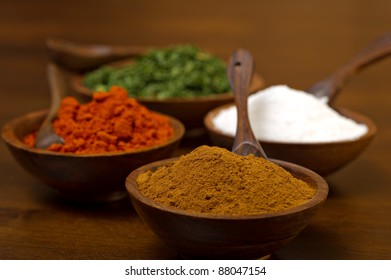 Wood bowls filled with colorful spices - cumin, paprika, salt and parsley flakes.  Each bowl has a wood spoon and are shot on a wood table.