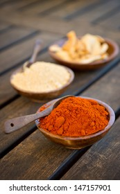 Wood bowls filled with paprika, ginger and shiitaki mushrooms. The first two bowls have a wood spoon. This is shot on a wood table.