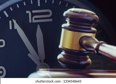 Wood and brass gavel standing upright on its base with a clock dial showing five to twelve behind in a law enforcement or auction concept