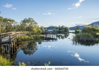 A wood bridge wraps along the edge of a pond reflecting in the calm waters in Kelowna British Columbia.