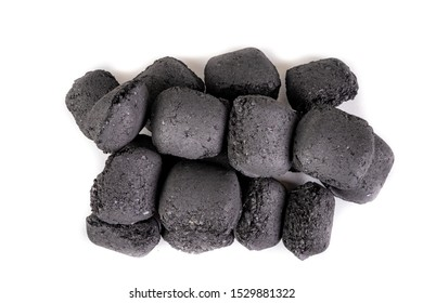Wood briquette used for grilling meat. Pressed charcoal for smoking in the grill. Light background.