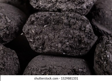 Wood briquette used for grilling meat. Pressed charcoal for smoking in the grill. Dark background.