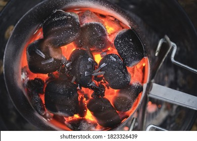 Wood briquettes are heated in a chimney starter on a charcoal grill. Close up.