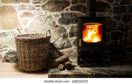 A wood burner drive and fireplace inside an old. stone cottage with logs and wicker storage basket.