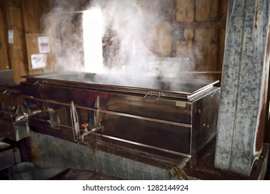 Wood burning evaporator with steaming sap for Maple syrup production in a sugar shack Kortright Centre for Conservation,  Woodbridge, Ontario, Canada - March 1, 2015
