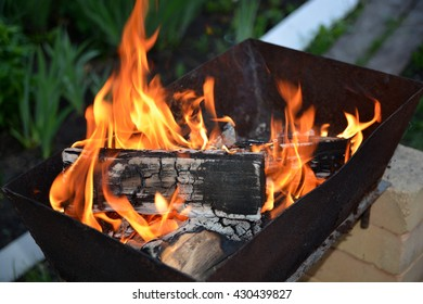 The wood burning in the fire on the grill